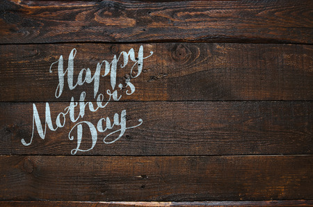 grunge wood: Happy Mothers Day lettering calligraphy on dark rustic barn wood holiday background.