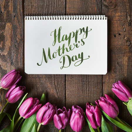 hapy: Hapy Mothers Day brush nib lettering calligraphy. Pink, tulips bunch on dark barn wood planks background. Stock Photo