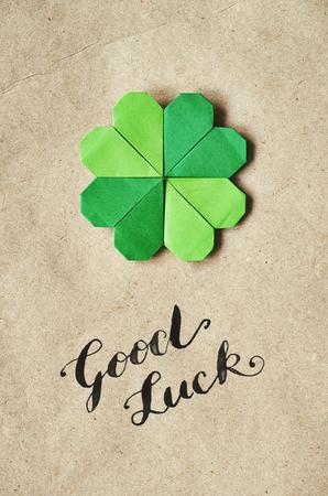 Emerald green paper folded origami clover shamrock leaf on craft paper eco background. Stock Photo