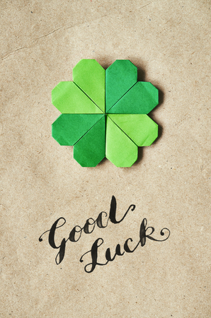 paper craft: Emerald green paper folded origami clover shamrock leaf on craft paper eco background. Foto de archivo