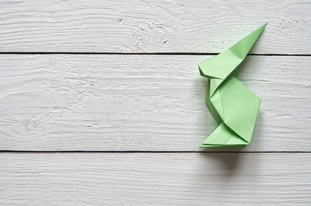 barn wood: Paper origami handmade bunny on white planks barn wood boards background.