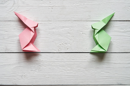barn wood: Paper origami handmade pink, green bunnies on white planks barn wood boards background Stock Photo
