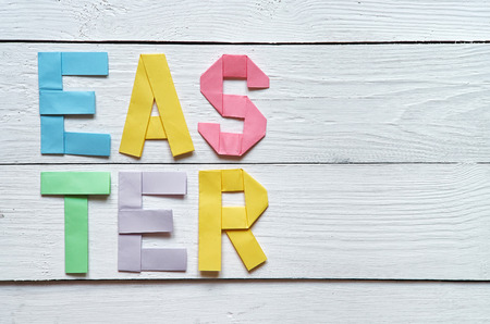 origami paper: Easter folded paper origami colorful lettering on white wooden planks rustic background.