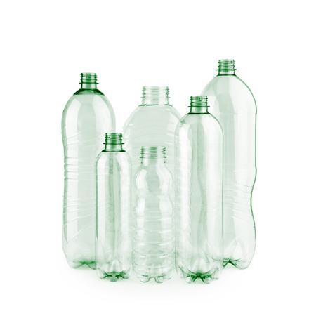 Seis nuevas y diversas botellas de plástico vacías verdes sin usar sin tapones sobre fondo blanco recortadas.