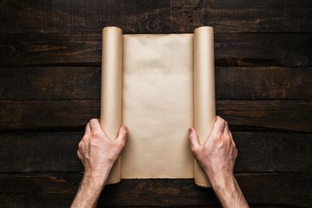 Manos del hombre que sostienen el rollo de papel estresado en el fondo antiguo de barwood. Concepto creativo de la expedición Wanderlust. Espacio vacío, espacio para texto, letras. Maqueta de banner horizontal.