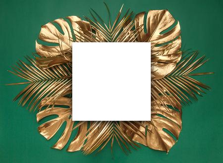 Hojas de monstera y palmera datilera tropical natural dorada brillante dispuestas creativamente sobre un fondo verde oscuro. Sala de tarjetas vacía en blanco para texto. Marco de borde fino de lujo. Foto de archivo