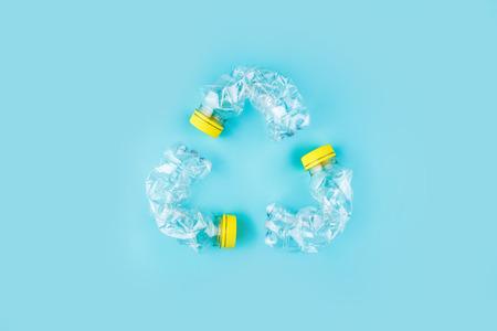 Tres botellas de plástico estrelladas sobre fondo azul forman un signo de reciclaje. Concepto de utilización de plástico. Cartel positivo atractivo problema ecológico. Foto de archivo
