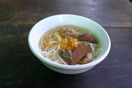 Mini bowl of steam Thai rice vermicelli with pig blood in clear soup topped with fried garlic on the dark wooden table