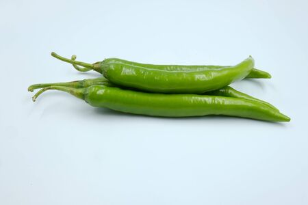 Fresh green whole chili peppers on the white background, organic ingredient for healthy, hot and spicy to help burning fat