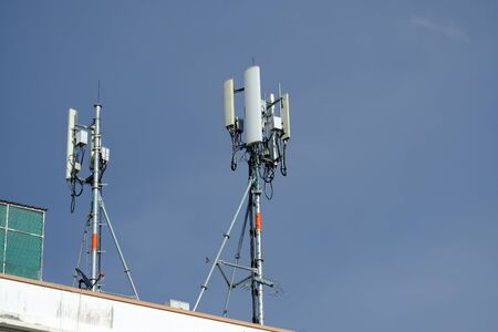 Telecommunication pole of 3G, 4G, 5G cellular antenna, small cell site base station on the rooftop of the building Foto de archivo