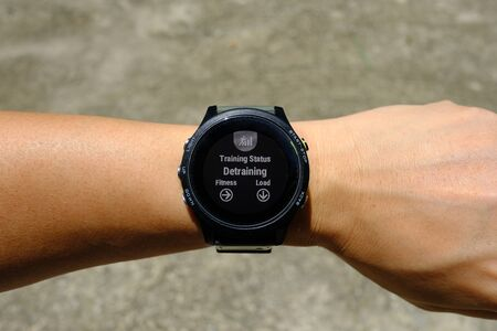 Training status on modern round-faced GPS multisport digital smartwatch on left hand wrist, detraining means decreasing load of training, selective focus.