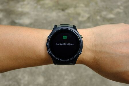 No notification status on modern round-faced GPS multisport digital smartwatch on left hand wrist, selective focus