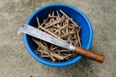 Knife on the edge of blue bucket, contain with Asian styled tiny firewood inside, preparation for cooking or warming, rural lifestyle of Asian traditional