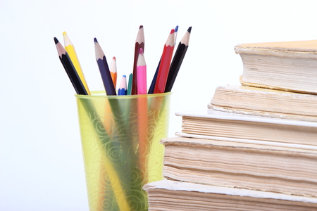 stack of old books. pencils in a glass on white background Banque d'images