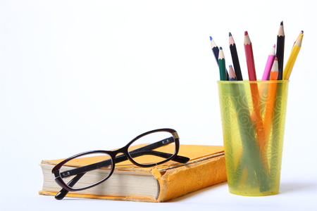 spectacles lying on old book. pencils in a glass on white background
