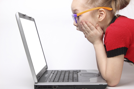 girl shocked by the laptop screen. white background. orange glasses