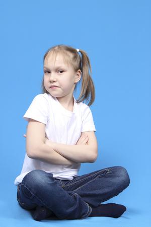 crosslegged: girl sitting cross-legged on a blue background