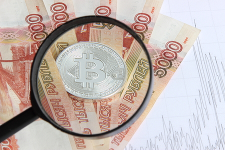 silver bitcoin on the background of banknotes