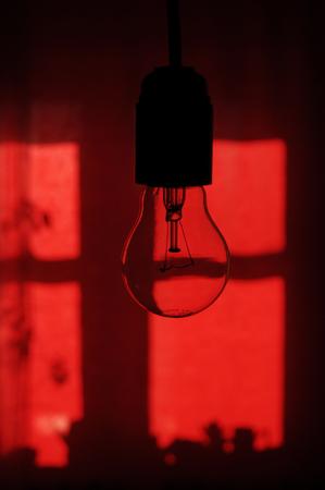 enchufe de luz: Bombilla de luz incandescente en el zócalo de la lámpara que cuelga en la textura de fondo de color rojo oscuro