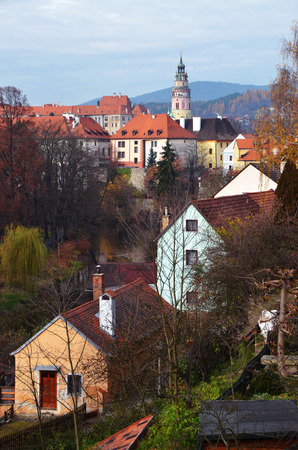 Cesky Krumlov, Czech Republic - November 10, 2012: Autumn view of the city Krumlov. In the foreground are small private buildings. Far away view of the Tower Little Castle. This is the oldest building of the castle complex. The tower was built in the XIII