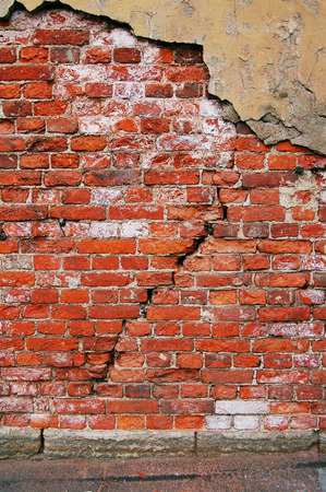 Red brick wall background. Large cracks in the center.
