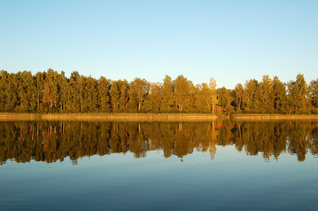 Russia. Reflection of forest in lake before sunset
