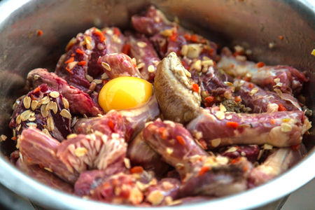 Natural, organic, healthy dog food (row meat, eggs and chiken bones) in metal bowl. Close up.