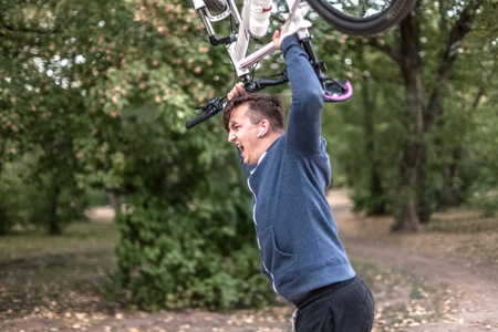 Young emotional cuacasian man crashes the bicycle holdlnig it up in both hands, angry expression on the face. Outdoors, autumn park background. Copy space. Funny picture, humor, concept. Crazy fitness, insurance for health, damned healthy lifestyle.