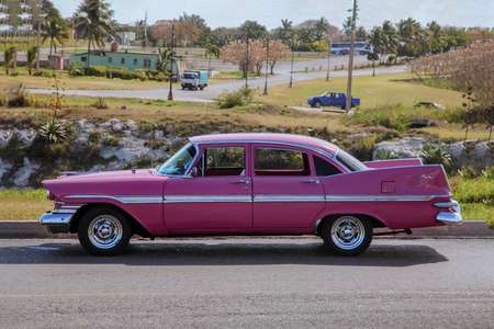 Classic vintage  retro car (pink Plymouth Fury 1959) from side proection, settled in front of a village landscape. Outdoor, copy space.