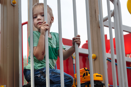 Cute caucasian blonde baby boy sits under the fence of children playground. Cute, serious and humile expression on the face, strong emotions of loneliness. Outdoor, copy space, yellow toy (grader).