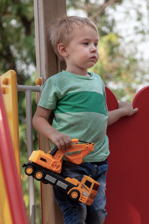 Cute caucasian blonde baby boy stands with a toy (yellow excavator) on the children playground. Alone, serious and humile expression on the face, strong emotions of loneliness. Outdoor, copy space.
