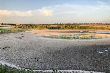 Great landscape with dry cracked earth (lake shore) and blue sky. Drought terrain. Unusual fantastic landscape. Outdoors, copy space. Standard-Bild