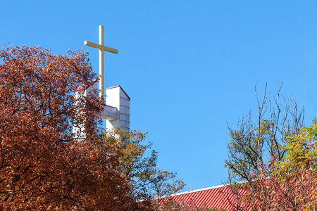 Cross peaking above the red roof of Catholic church on the blue sky background; autumn trees on the front view. Outdoors, copy space.