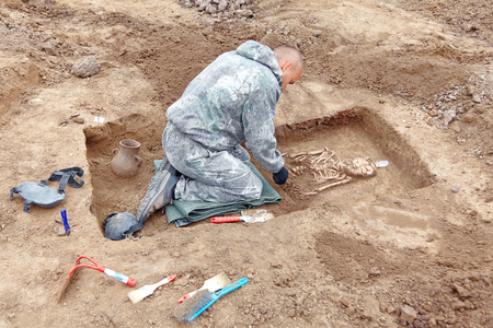 Archaeological excavation. The archaeologist in a digger process. Leaning to the tomb, hands with tools, conducting research on human bones, part of skeleton and skull in the ground, shovel and brush near. Close up, outdoors. Reklamní fotografie
