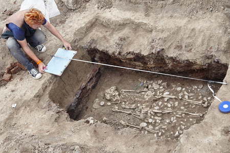 Archaeological excavations. Young stylish archaeologist with red hair makes drowings of human bones, skeleton and skull in the ground tomb. Real digger process. Outdoors, copy space. Standard-Bild