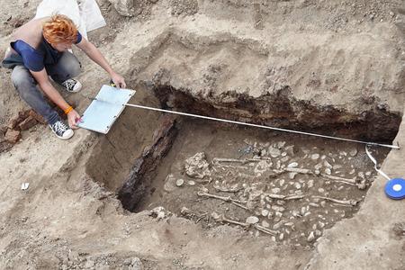 Fouilles archéologiques. Un jeune archéologue élégant aux cheveux roux fait des noyades d'os humains, de squelette et de crâne dans la tombe au sol. Véritable processus de pelle. À l'extérieur, copiez l'espace. Banque d'images