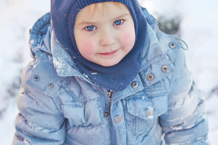 Hat and hoodie on winter background. Healthy childhood. Outdoors, winter activity. Copy space, close up portrait.