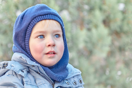 Winter clothes and hat (hood) on green background. Healthy childhood. Outdoors, copy space, close up portrait.
