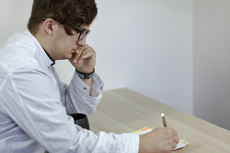 Young caucasian male doctor in a white outfit writes something sitting on the table with cup of tea or coffee. Serious face expression, glasses, finger ring. Indoors, copy space.