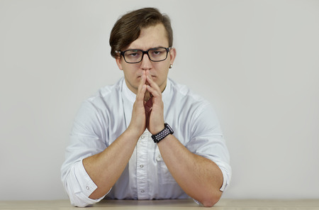 Young caucasian very serious male in white robe sits frowning, hands on the table. Feeling look, strong emotions. Electronic watch gadget on one hand, glasses and earring. Indoors, copy space.