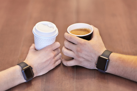 Two hands, male and female, both with equal electronic wrist watches, holding cups of coffee, white and black, on the wooden table. Date or friends meeting. Indoors, copy space.
