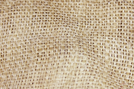 Close up picture of crumpled old burlap background. Ecological, natural fabric packing issue, rustic jute backdrop. Copy space.