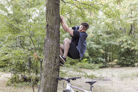 Young funny caucasian man climbs up to the tree with fair or horror, white bicycle stands down below. White wireless earphones, casual sportswear. Outdoor, abandoned park of forest, copy space. 스톡 콘텐츠