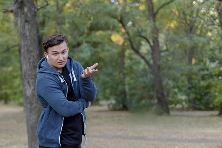 Young handsome caucasian man with perplexed face expression and skeptical gesture at green park, wearing casual. Outdoors, copy space, strong emotions.
