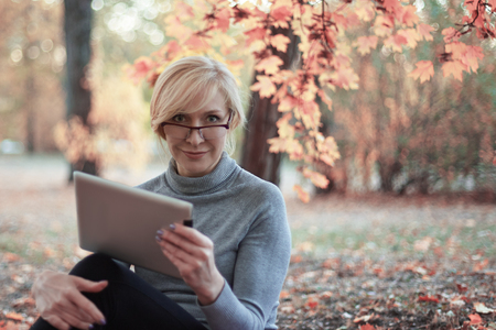 Middle aged caucasian woman sits alone at park, smiling. Casual wear, glasses. Precious age concept. Outdoors, copy space. 版權商用圖片