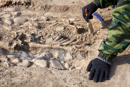 Archaeological excavations. The archaeologist in the digger process, the human bones Hands with brush. Close up, outdoors, copy space. Reklamní fotografie