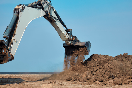 Excavator loader working at ground area on blue sky background, digging process. Bucket up scoops ground.. Outdoors, copy space.