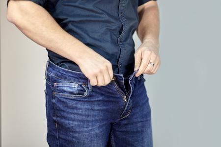 L'uomo apre i jeans blu. Torso uomo, dito, camicia blu, abbigliamento casual. All'interno, sfondo grigio vuoto, copia spazio.
