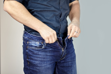 Man unzipps blue jeans. Man torso, fingerring, blue shirt, casual wear. Indoors, grey empty background, copy space.