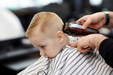 Cute blond baby boy with blue eyes in a barber shop having haircut by hairdresser. Hands of stylist with tools. Children fashion in salon. Indoors, dark background, copy space. Imagens